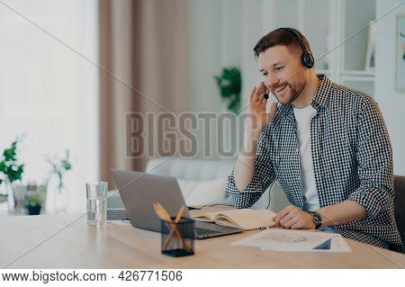 Horizontal Shot Of Cheerful Man Participates In Self Improvement Webinar Wears Checkered Shirt Commu