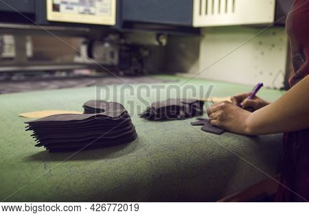 Shoe Factory Worker Making Design For New Footwear Standing At Table With Cut Out Details