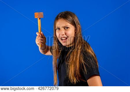 Pretty Preteen Girl Attacking With A Wooden Kitchen Mallet In Self Defense On Blue Studio Background