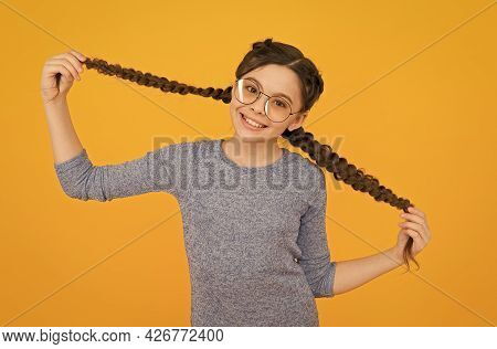 Interested In My Hair And My Hairdresser. Happy Girl Hold Hair Braids Yellow Background. Small Child