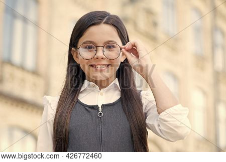 Happy Girl Child Wearing School Uniform Fix Eyeglasses In Fashion Frame To See Clearly Outdoors, Opt