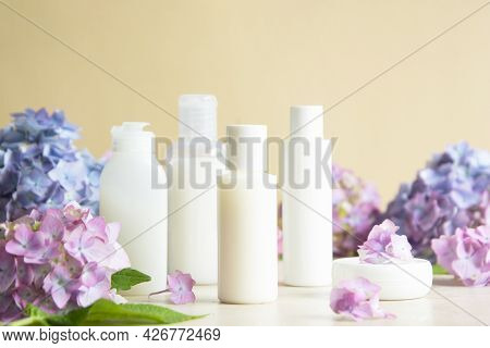 Cosmetic Bottles Blank Mockup And Hydrangea Flowers On Background. Body, Skin Care