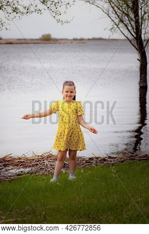 Lifestyle Full-length Portrait Of A Girl In A Yellow Dress On The Riverbank Enjoying A Warm Spring D