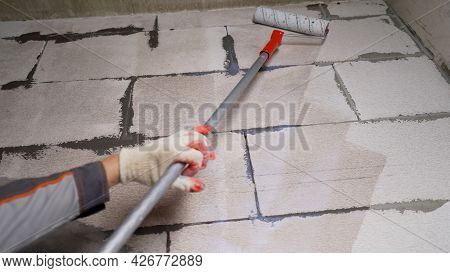 An Industrial Technician Primes The Wall Of A Building With A Roller. Priming The Walls With A Rolle