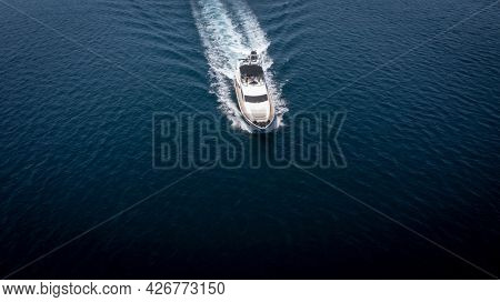 Aerial view of luxury speedboat yacht cruising in deep ocean water, symbol of wealth and luxury travel.