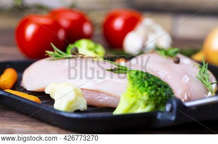 Raw Chicken Fillet With Garlic, Pepper And Rosemary On A Wooden Background.