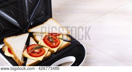 Making Cheese And Tomato Sandwiches On A Sandwich Press.