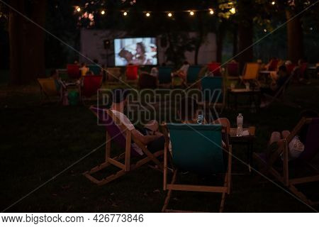Real People Watching Movie In The Open Air Cinema In The Evening, Summer Leisure And Outdoor Recreat
