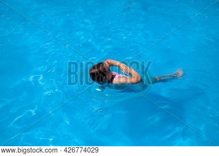 Summer Postcard With A View Of The Sea And A Child Floating In A Blue Inflatable Circle On The Sea,