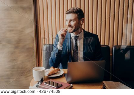 Young Male Investor Dressed In Blue Suit Looking Outside Window While Sitting In Cafe Hearing Good N