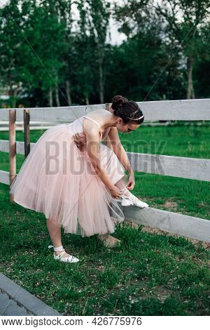Lifestyle Full-length Portrait Of A Ballerina In A Pink Dress With A Full Organza Skirt Bends Down T