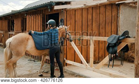 Female Jockey Placing A Saddle Pad On Her Light Brown Horseback To Protect From Sweat And Sores. Blu