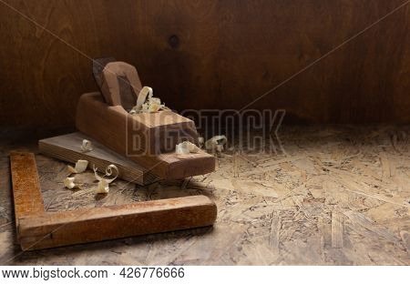 Woodworking tools on wooden table. Plane jointer carpenter or joiner tool and wooden shavings. Carpentry workshop