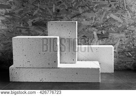 Aerated concrete block cube or bricks near osb wall background texture. Construction concept of minimalism design