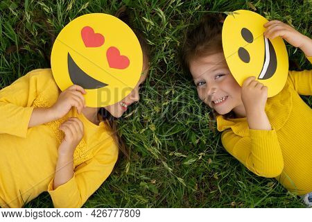 Little Girls Are Lying On The Lawn Covering Part Of Their Faces With Emoticons And Laughing Merrily.