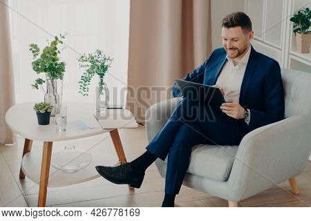 Young Happy Business Professional Wearing Suit Working On Laptop And Smiling, Enjoying Online Video