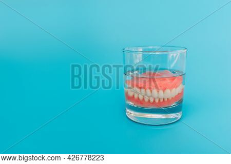 Prosthesis In A Glass With A Solution. Dental Prosthesis Care. Full Removable Plastic Denture Of The