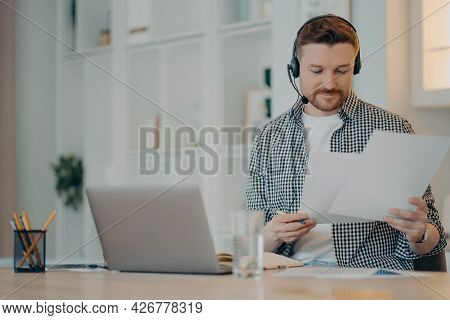Busy Male Freelancer Wearing Headset Holding Documents In Hands And Working Remotely On Laptop While