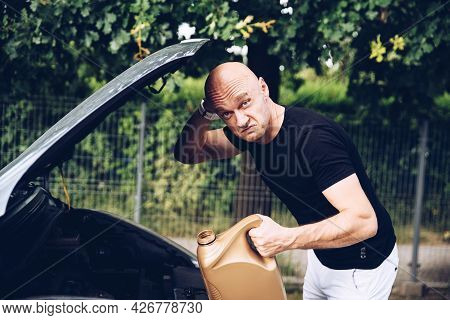 Surprised Man Checks The Engine Oil Level Of The Car.