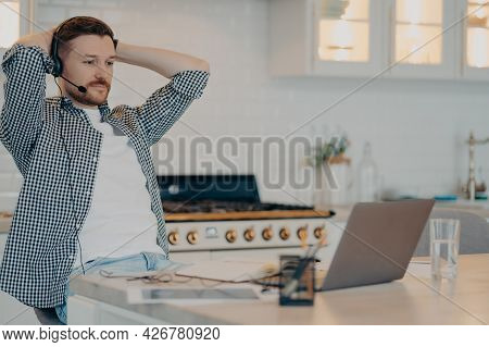 Enjoying Remote Work. Relaxed Bearded Male Freelancer Sitting At Table And Resting After Video Meeti