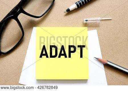 Adapt. Text On The Sticker. Bright Sticker On Craft Background