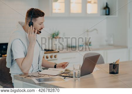 Side View Of Focused Bearded Call Manager Or Freelancer Sitting At Desk With Laptop In Modern Kitche