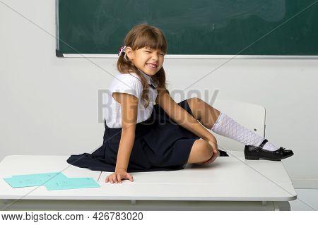 Happy School Girl Sitting On Desk In Classroom. Joyful Girl Student In White Blouse And Blue Skirt R