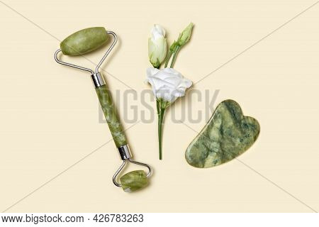 Green Jade Roller And Gua Sha Stone For Facial Massage And Tender White Flower Eustoma On Pastel Yel