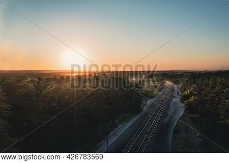 Shiny Rails At Turn Of Railway Among Coniferous Forest At Sunset On A Clear Summer Day. Picturesque