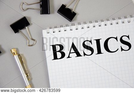 Basic Word Written On Gray Background With Pencils And Paper Clips