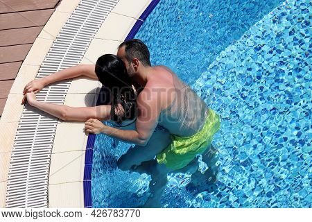 Passionate Couple Embracing And Kissing In The Pool Water. Romantic Vacation Or Honeymoon, Passion A
