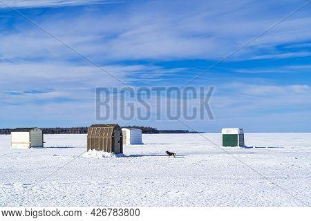 Ice Fishing On A Frozen Harbor Along The Coast Of Prince Edward Island, Canada.