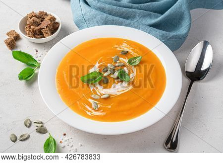 Pumpkin Cream Soup With Cream And Pumpkin Seeds In A White Plate On A Gray Background With A Spoon A