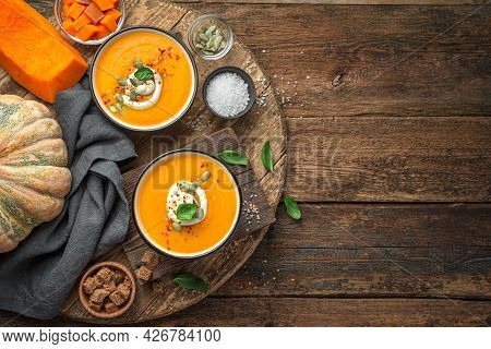 Pumpkin Soup With Cream, Spices And Basil In Two Serving Bowls On A Natural Wooden Background. Autum