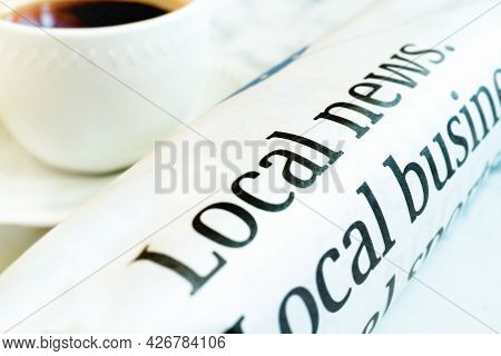 Rolled Up Morning Paper Along Side A Cup Of Coffee.