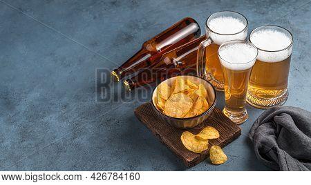 Three Beer Mugs, Chips And Beer Bottles On A Dark Blue Background. Beer Party, Oktoberfest. Side Vie