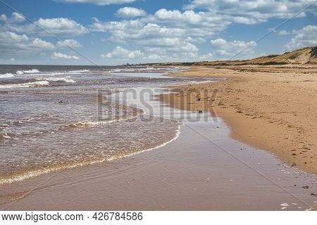 Waves Lap Up On A Sandy Beach On The North Shore Of Prince Edward Island, Canada.