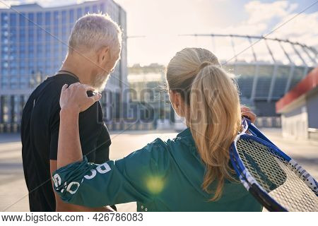 Back View Of Sportive Middle Aged Couple, Tennis Players With Tennis Racket Standing Together Outdoo