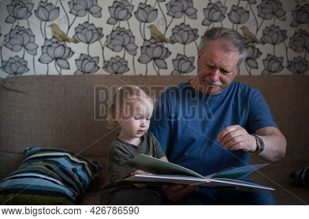 Grandfather And His Small Graddaughter Reading Book Together On A Couch. Family Time And Generation