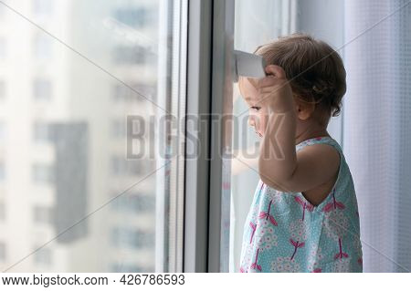 Small 1 Year Old Pensive Girl Against Closed Window Looking Out. Quarantine And Self-isolation Conce