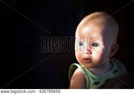 Contrast Emotional Portrait Of Surprised Baby. Light And Shadow, Dark Background, Copy Space.