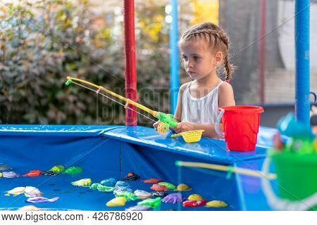 Child Fisher Catching Plastic Toy Fish On Pool Amusement Park Summer Day Little Girl Have Fun On Fis