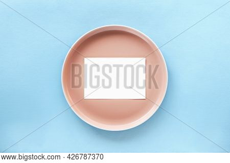 Pink Plate With Blank Business, Greeting Card, Invitation Mockup. Blue Background. Top View, Flat La