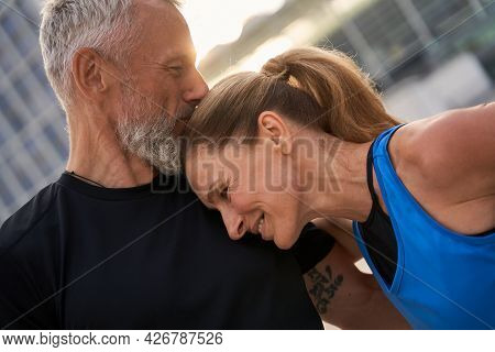 Portrait Of Affectionate Middle Aged Couple, Man And Woman In Sportswear Having Morning Workout In T