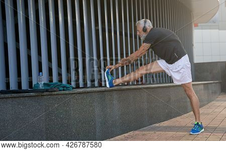 Full Length Shot Of Sportive Middle Aged Man In Sportswear And Headphones Warming Up His Body, Getti