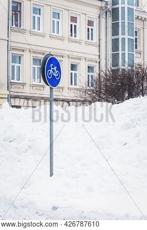 Road Sign Of Bicycle Path On City Street Covered With Snowdrift. Concept Of Seasons, Seasonal Sport
