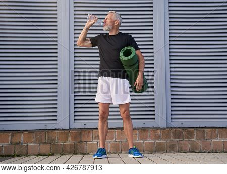 Sportive Middle Aged Man Drinking Water, Holding Exercise Mat, Ready For Doing Sport Outdoors