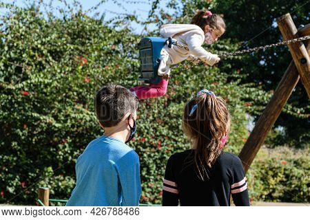 A Boy And A Girl With Their Backs Turned, Watching A Child Playing On The Swing.
