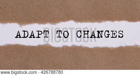 Adapt To Changes Word Written Behind Torn Paper. Business Concept