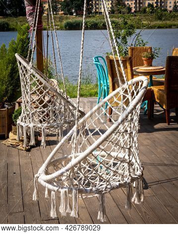 Two White Macrame Chair Swings With Tassels On Bottom, And A Garden Furniture On A Bright Wooden Pat